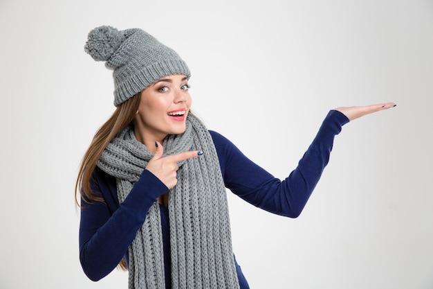 Retrato de uma mulher sorridente em um pano de inverno, mostrando o copypace na palma da mão isolado em um fundo branco