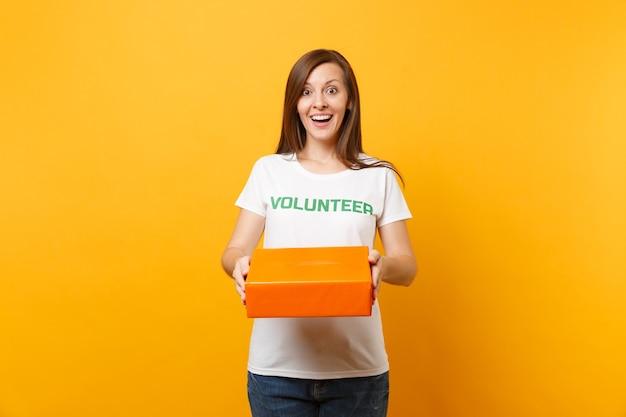 Retrato de uma mulher sorridente em uma camiseta branca com voluntário de título verde de inscrição escrita segura caixa de papelão laranja isolada em fundo amarelo. ajuda de assistência gratuita voluntária, conceito de graça de caridade