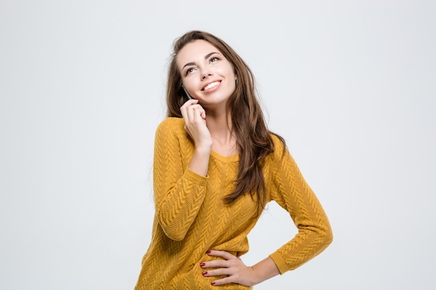 Retrato de uma mulher sorridente falando ao telefone, isolado em um fundo branco