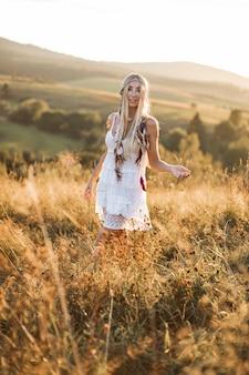 Retrato de uma mulher sorridente feliz com longos cabelos loiros está usando vestido branco hippie boho em campo