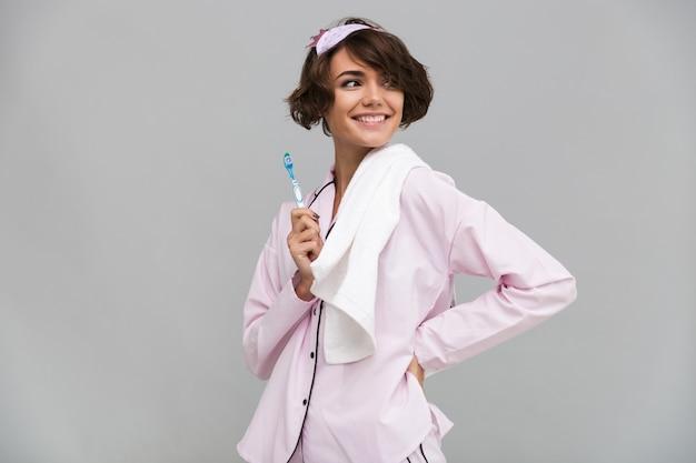 Retrato de uma mulher sorridente feliz de pijama e toalha