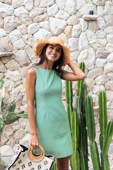 Retrato de uma mulher sorridente feliz e elegante com um vestido verde elegante de verão segurando uma bolsa e um chapéu de palha no fundo da parede de pedra branca e cacto