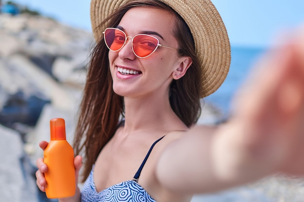 Retrato de uma mulher sorridente feliz em um maiô, chapéu de palha e óculos de sol vermelhos brilhantes com uma garrafa de protetor solar durante o banho de sol à beira-mar no mar em tempo ensolarado no verão
