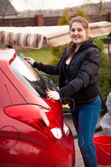 Retrato de uma mulher sorridente lavando um carro vermelho no quintal