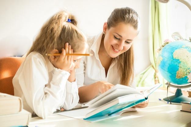 Retrato de uma mulher sorridente lendo um livro com a filha na mesa