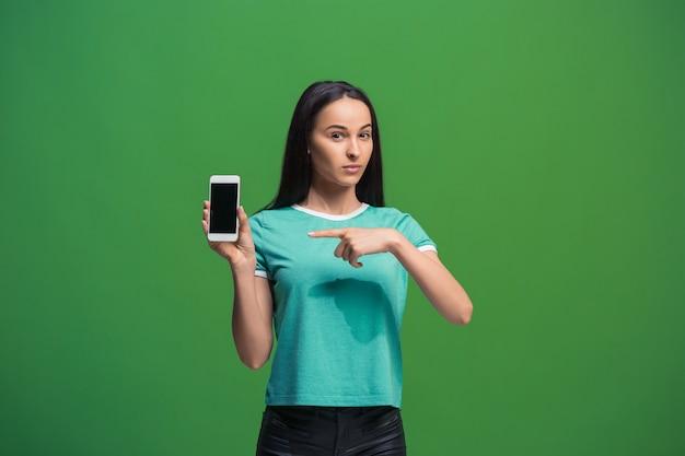 Retrato de uma mulher sorridente, mostrando a tela do smartphone em branco, isolada em um fundo verde