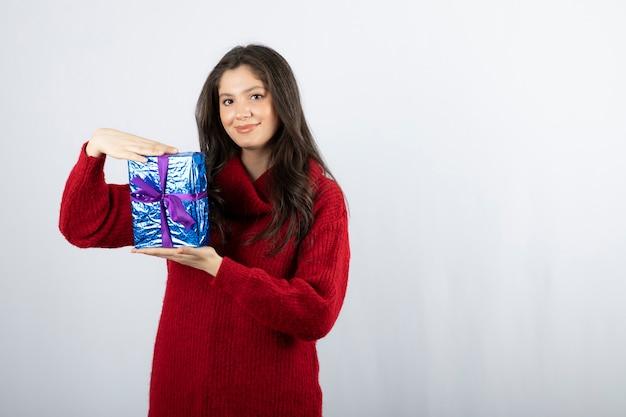 Retrato de uma mulher sorridente, mostrando uma caixa de presente de natal com fita roxa.