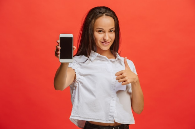 Retrato de uma mulher sorridente no vestido vermelho, mostrando a tela do smartphone em branco