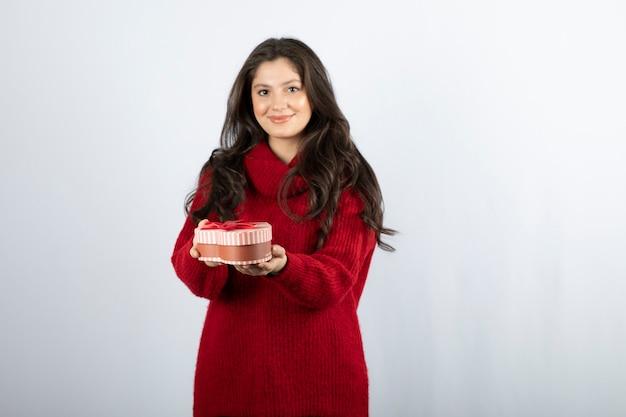 Retrato de uma mulher sorridente, oferecendo uma forma de coração de caixa de presente sobre uma parede branca.