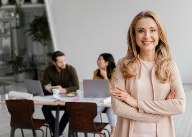 Retrato de uma mulher sorridente posando ao lado de seus colegas