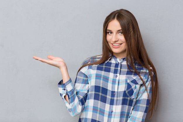 Retrato de uma mulher sorridente segurando copyspace na palma da mão sobre uma parede cinza