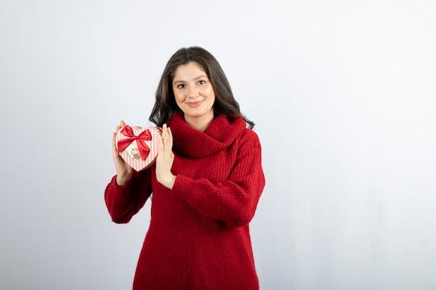 Retrato de uma mulher sorridente, segurando em forma de coração de caixa de presente de mãos sobre uma parede branca.