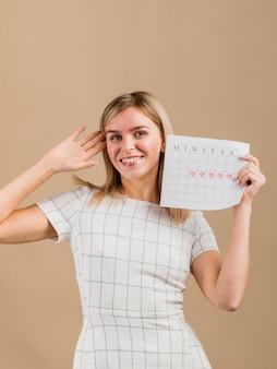 Retrato de uma mulher sorridente segurando o calendário do período