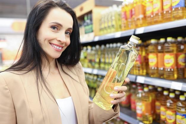 Retrato de uma mulher sorridente segurando óleo de girassol em uma loja