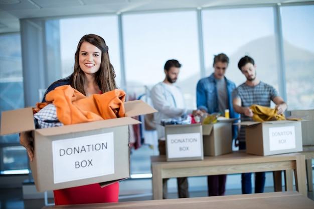 Retrato de uma mulher sorridente segurando uma caixa de doações no escritório
