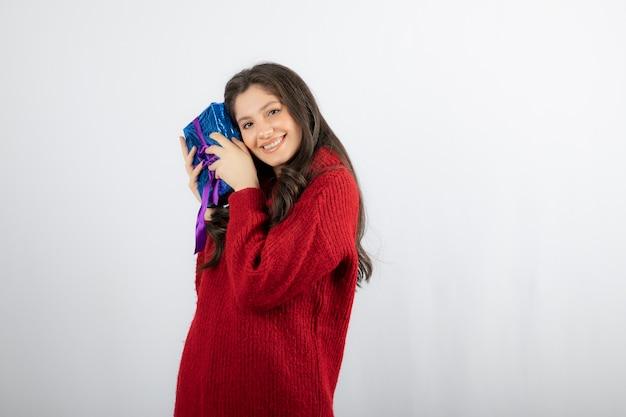 Retrato de uma mulher sorridente, segurando uma caixa de presente de natal com fita roxa.