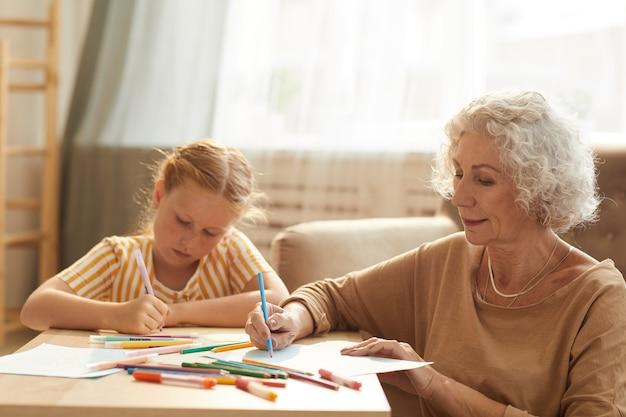 Retrato de uma mulher sorridente sênior cuidando de uma linda garota ruiva e desenhando juntos enquanto estão sentados à mesa de centro na aconchegante sala de estar