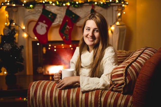 Retrato de uma mulher sorridente, sentada na cadeira perto da lareira e bebendo chá