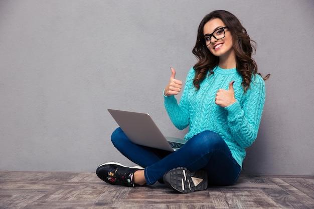 Retrato de uma mulher sorridente, sentada no chão com um laptop e mostrando os polegares na parede cinza