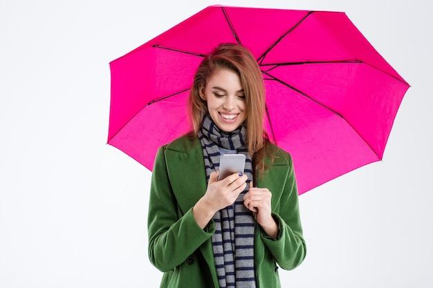 Retrato de uma mulher sorridente usando smartphone sob o guarda-chuva isolado em um fundo branco