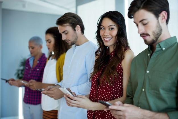 Retrato de uma mulher sorridente usando telefone celular com seus colegas de escritório