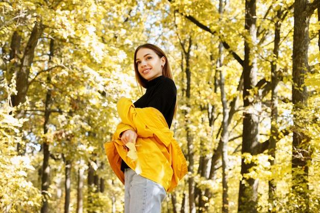 Retrato de uma mulher sorrindo no contexto de uma floresta de outono amarelo