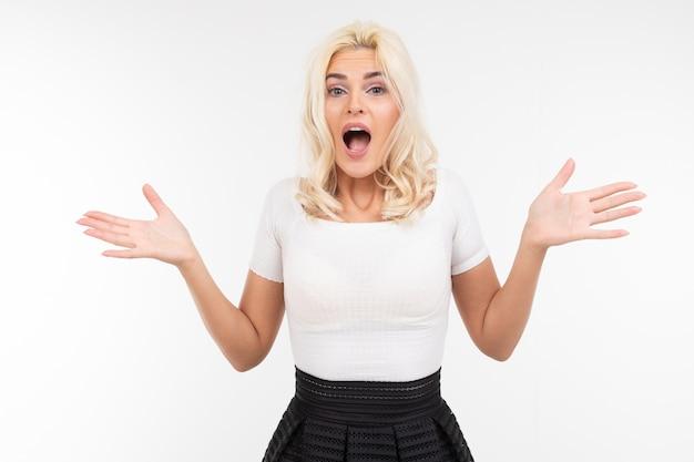 Retrato de uma mulher surpreendida em uma camiseta branca com a boca aberta, agitando os braços para os lados em um fundo branco