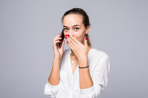 Retrato de uma mulher surpresa e impressionada com olhos arregalados e boca aberta, atordoada por algo que está ouvindo no telefone enquanto está encostada em uma parede cinza. garota usa algum aplicativo