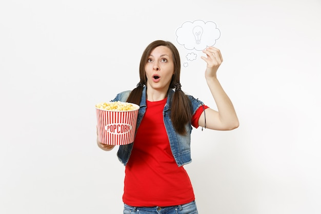 Retrato de uma mulher surpresa em roupas casuais, assistindo ao filme do filme, segurando, digamos, nuvem com lâmpada, ideia e balde de pipoca isolado no fundo branco. emoções no conceito de cinema. balão de fala