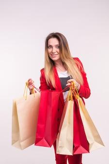 Retrato de uma mulher surpresa em um terno vermelho com sacolas de compras.