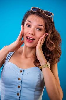 Retrato de uma mulher surpresa usando óculos escuros na parede azul