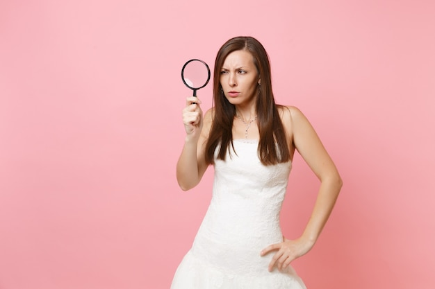 Retrato de uma mulher suspeita em um vestido branco examinando olhando através de uma lupa