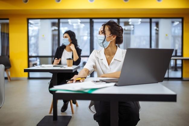 Retrato de uma mulher trabalhando em um laptop em uma mesa de escritório, usando máscara médica e protegendo-se durante o surto de pandemia covid-19.