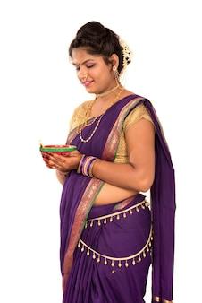 Retrato de uma mulher tradicional indiana segurando uma foto de diya, diwali ou deepavali com mãos femininas segurando uma lamparina durante o festival da luz