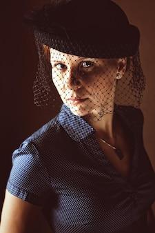 Retrato de uma mulher triste com um chapéu com um véu no funeral mulher atraente e solitária com chapéu