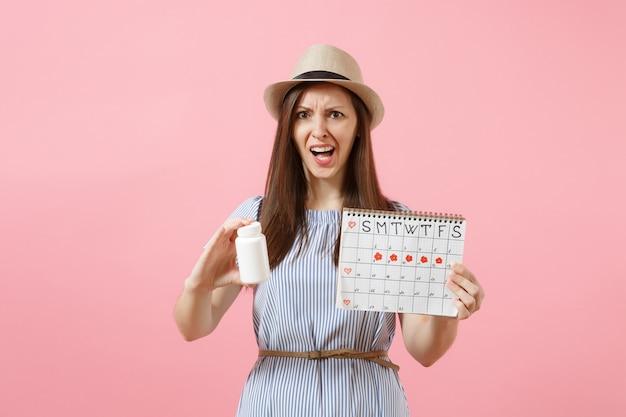 Retrato de uma mulher triste em um vestido azul, segurando o frasco branco com comprimidos, calendário de períodos femininos, verificando os dias de menstruação isolados no fundo. saúde médica, conceito ginecológico. copie o espaço.