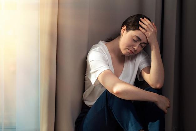 Retrato de uma mulher triste, segurando a cabeça, sentada no canto do apartamento. copie o espaço. o conceito de violência doméstica.
