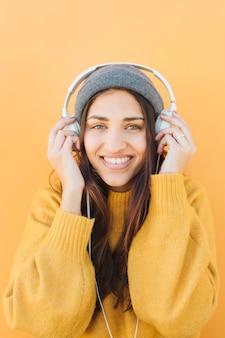 Retrato de uma mulher usando fones de ouvido contra a superfície colorida