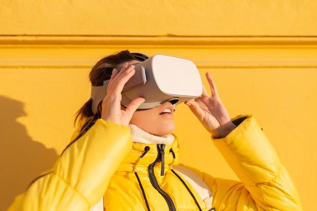 Retrato de uma mulher usando óculos de realidade virtual na rua contra uma parede amarela sob a luz do sol no inverno em roupas quentes