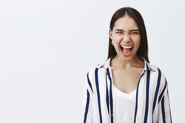 Retrato de uma mulher zangada, doente e cansada, com uma blusa listrada, enrugando o nariz e franzindo a testa enquanto grita de raiva