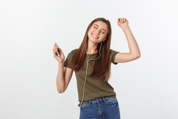 Retrato de uma música de escuta da mulher bonito alegre nos fones de ouvido e na dança isolados em um branco.