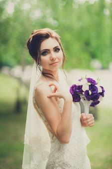 Retrato de uma noiva andando sozinho com buquê nas mãos no parque no dia do casamento