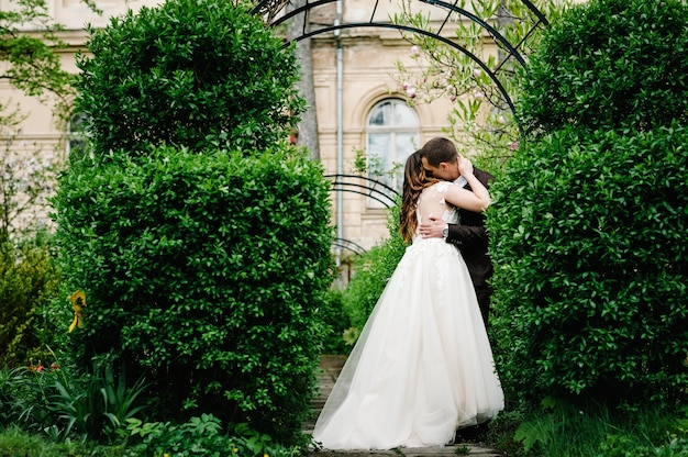 Retrato de uma noiva atraente que abraça e beijando o noivo.