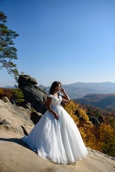 Retrato de uma noiva bronzeada em um fundo de montanhas. sessão de fotos pós-casamento enquanto viaja em ...