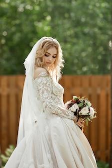 Retrato de uma noiva com um vestido de noiva e um buquê de flores nas mãos.