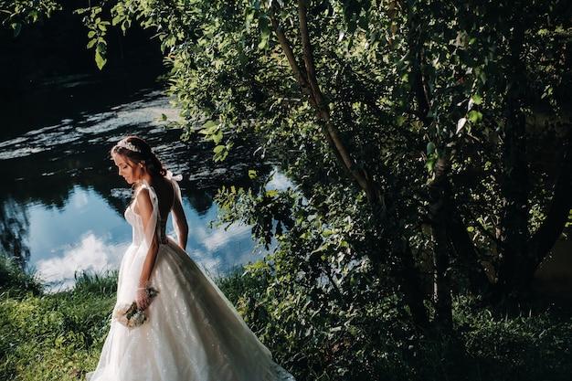 Retrato de uma noiva elegante em um vestido branco com um buquê na natureza em um parque natural. modelo em um vestido de noiva e luvas e com um buquê.