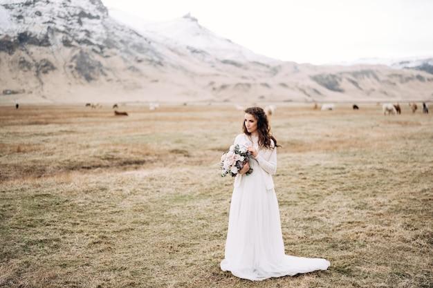 Retrato de uma noiva em um vestido de noiva branco com um buquê de noivas nas mãos em um campo seco