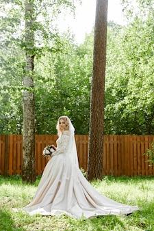 Retrato de uma noiva em um vestido de noiva com um buquê de flores nas mãos
