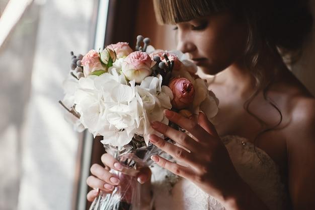 Retrato de uma noiva linda com um buquê de rosas e hortênsia interior. noiva muito feliz num vestido de luxo perto da janela. preparação da manhã do casamento