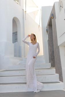 Retrato de uma noiva linda em um vestido branco. uma menina levanta em um fundo das etapas brancas e paredes brancas em oia, santorini.
